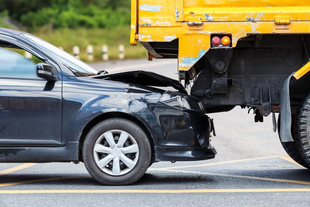 car crashing on a trucks rear-end