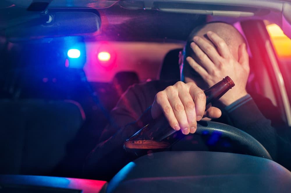 drunk driver holding a beer bottle
